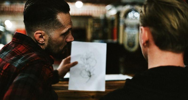 tatuażysta pokazuje klientowi rysunek